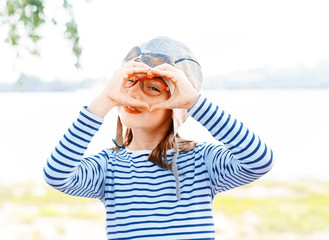 Adorable little girl in a shirt with horizontal stripes and orange glasses smiles looking through her heart-shaped hands
