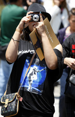 A fan of Michael Jackson takes a picture as she leaves the Staples Center following the Michael Jackson Memorial service in Los Angeles