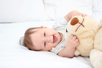 Cute baby playing with teddy bear on bed