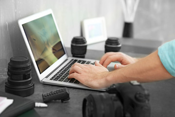 Photographer working with laptop in office