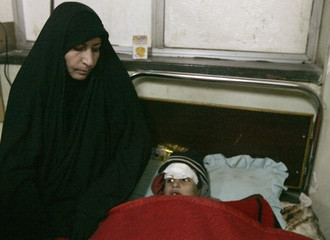 A woman sits near her son, wounded in a bomb attack, in a hospital in Baghdad's Sadr City