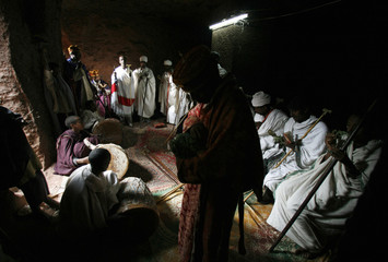 Priests sing and play drums in a small grotto next to Saint George after the morning mass in Lalibela