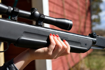 Woman holding and aiming with the air rifle.