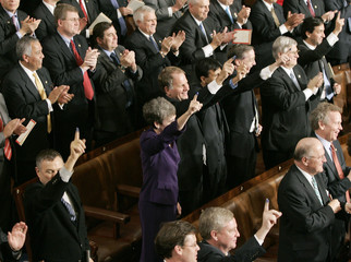 U.S. President George W. Bush delivers his State of the Union address as members hold up inked fingers.