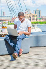 Young African American Man traveling, working on laptop computer in New York