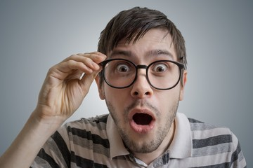 Nerdy man has open mouth and is surprised and shocked.