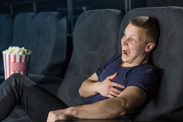 Young man screaming while watching a movie at the cinema