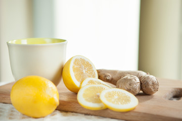 Ginger and yellow lemon with cup as healthy food concept