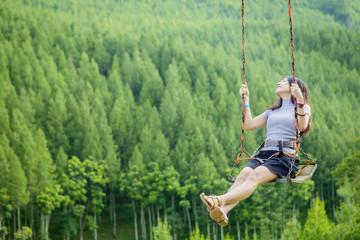 Joyful woman playing on swing
