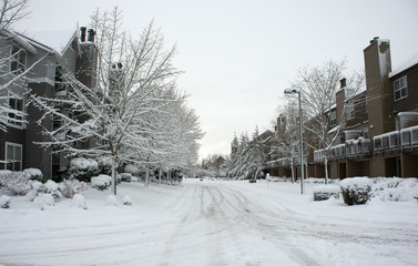 A snow covered residential roadway between two residential apartment buildings