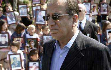The U.S. ambassador to the UN, Zalmay Khalilzad, passes near the children of Mala Krusa