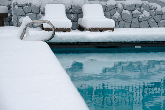 An outdoor swimming pool. the area around it and the lounging chairs  covered in over half a foot, 20cm, of snow.
