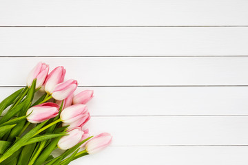 Pink tulips on white wooden background. Top view, copy space