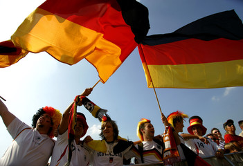 German soccer fans wave flags as they watch the World Cup soccer match between Germany and Argentina in Gelsenkirchen