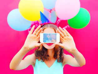 Display of phone woman in a birthday cap is taking a picture on a smartphone with an air colorful balloons on a pink background