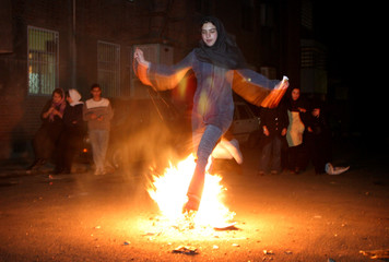 Iranian woman jumps over a fire during a traditional ceremony in Tehran.