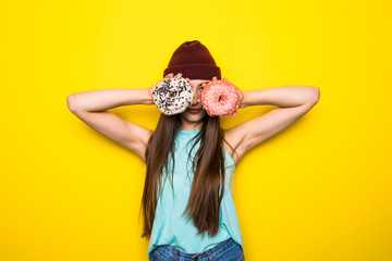 Slim hipster woman making glasses with two donutes yellow background