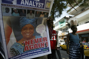 A woman walks past a man reading a newspaper in Monrovia
