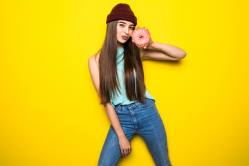 beautiful excited hipster girl in red hat holding pink donut near yellow wall