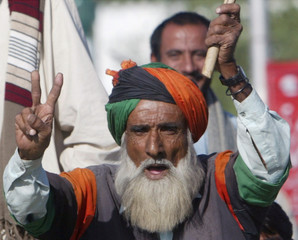 A supporter of former PM Benazir Bhutto gesture  as they gather outside Karachi airport to greet their returning leader