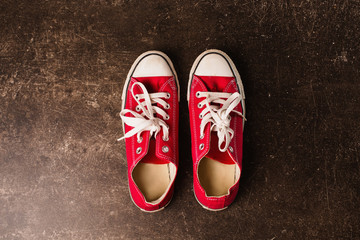Red sneakers on a dark marble background. Footwear for outdoor activities