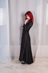 Beautiful girl with red hair and natural make-up and pale skin. A woman in a black retro dress. Model posing in studio. The unusual appearance. Insidious wicked witch woman.