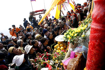 Buddhists gather around the Chua Dong or Bronze Pagoda to pray during its completion ceremony at the Yen Tu mountain