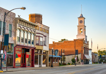 Main street of rural small town in midwest USA with storefronts and clock tower Wall mural