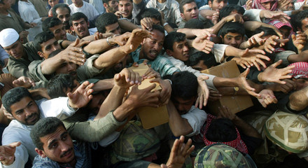 Iraqi men crush to try to get food packages handed out by British soldiers from the Tactical Supply ..