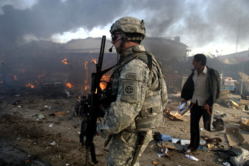 A U.S. soldier walks after a car bomb explosion at a market in the neighbourhood known as New Baghdad