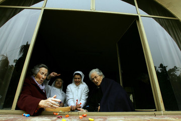 Elderly women and nuns collect sweets which are thrown from a float during the traditional Epiphany ..