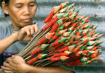 A FILIPINO WORKER INSPECTS ROCKETS IN BOCAUE.