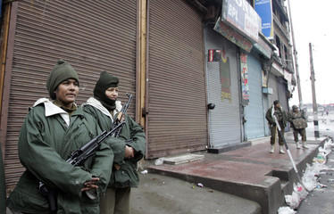 Indian policewomen stand guard in front of closed shops during the sixth phase of local elections in Srinagar