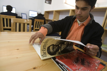 Afghan man looks at an U.S. published book with a picture of former U.S. president Abraham Lincoln as he sits at the Lincoln U.S. support library in Herat