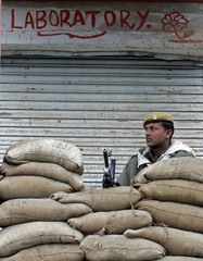Indian policeman guards polling station during first phase of local elections in Ajas