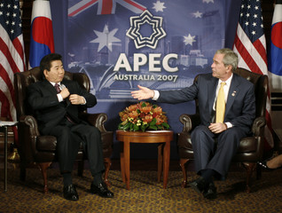 U.S. President W. Bush reaches out to shake hands with South Korea's President Roh Moo-hyun in Sydney