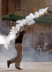 Palestinian youth throws tear gas canister towards Israeli troops during clashes near Nablus