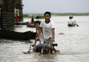 Boys ride a tricycle along a flooded street in San Agustin village in Pampanga province north of Manila