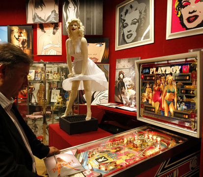 A visitor plays the pinball machine playboy in front of a sculpture of Marylin Monroe in the showroom of Drouot auction house in Paris