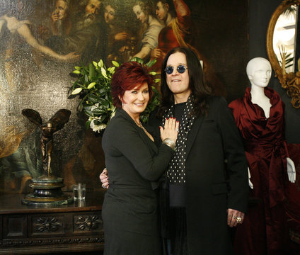 Ozzy and Sharon Osbourne pose in front of some of their belongings in Beverly Hills