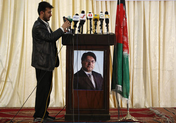 Reporter puts his microphone on podium which has picture of former Afghan FM and presidential candidate Ahadi during campaign in Kabul