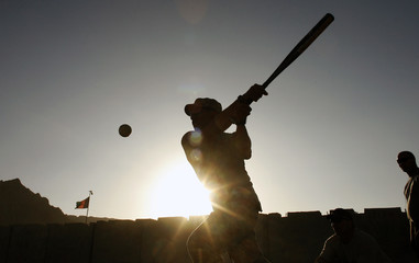 Sgt. Chin from the U.S. Army hits a ball during a softball game at FOB Altimur