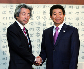 Japanese Prime Minister Koizumi shakes hands with South Korean President Roh in Pusan, South Korea