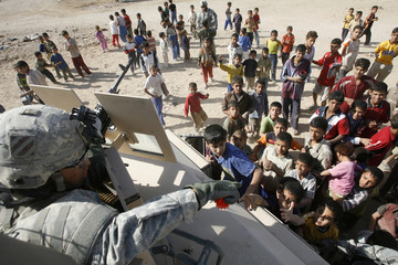 A U.S. soldier from First Battalion, 10th Field Artillery distributes toys to children in the outskirts of Baghdad