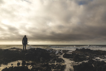 Fisherman Standing on Rocky Shore