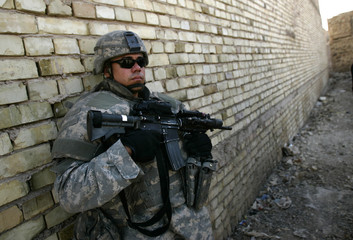 U.S. soldier takes up position during a patrol in Zafraniya neighbourhood, southeast of Baghdad