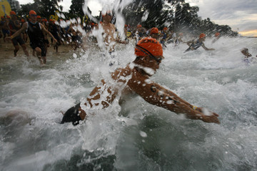 Competitors dive into the water during the start of the Aviva Ironman 70.3 triathlon in Singapore