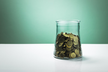 money in a glass bottle on white table and green wall background ,savings concept