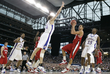 Davidson Wildcats guard Curry tries to get off shot against Kansas Jayhawks center Kaun during NCAA men's Midwest Regional finals basketball game in Detroit
