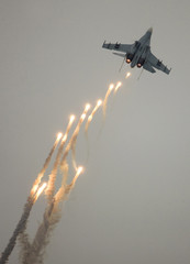 "A jet fighter releases flares during a military festival at the ""Stalin Line"" memorial near the village of Goroshki"